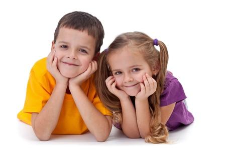 Beautiful felices los niños que están en el suelo-niño y una niña, aislados