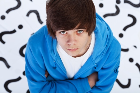 Quest of life - teenager boy wondering over question marks background photo