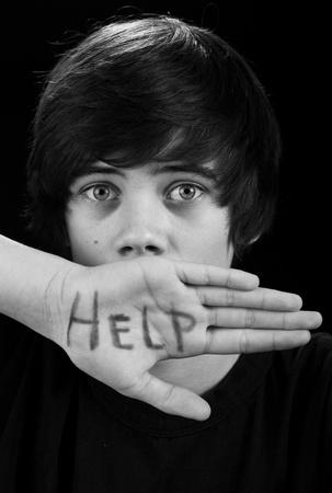 needing: Teenager with scared look needing help - on black background Stock Photo