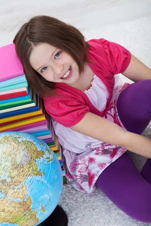 Happy school girl with books and globe sitting on the floor