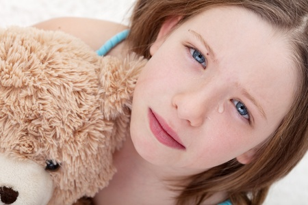 Beautiful sad girl holding teddy bear and crying - closeup photo