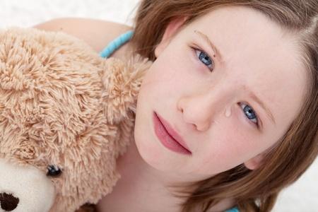 verdrietig meisje: Mooie verdrietig meisje met teddybeer en huilen - close-up Stockfoto
