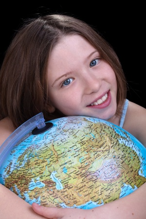 Young girl dreaming about a trip - holding a globe, closeup photo