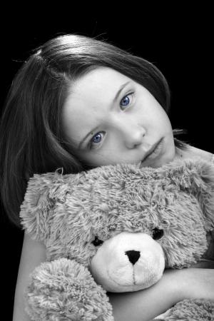 Sad young girl with amazing eyes hugging her teddy bear photo