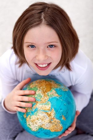 hands holding earth: Young girl studying geography with an earth globe Stock Photo