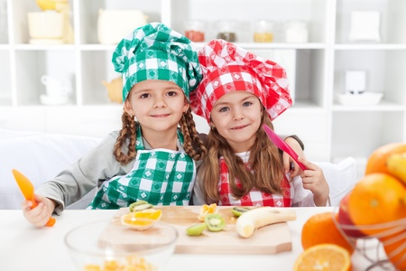 Little chef girls slicing fruits in the kitchen - healthy eating photo