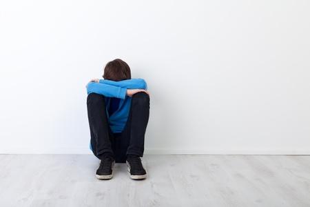 depressione: Adolescente ragazzo Sad seduto sul pavimento vicino al muro
