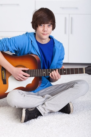 Young teenager boy playing the acoustic guitar photo