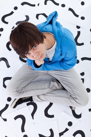 Young teenager boy with lots of questions looking up photo