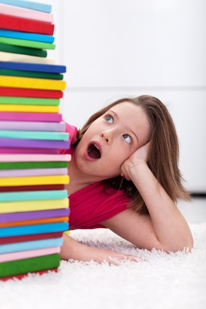 Young school girl looks shocked at a large stack of books Stock Photo - 12477450