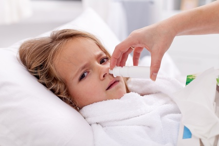 catarrh: Little girl with bad cold using nasal spray and upset about it Stock Photo