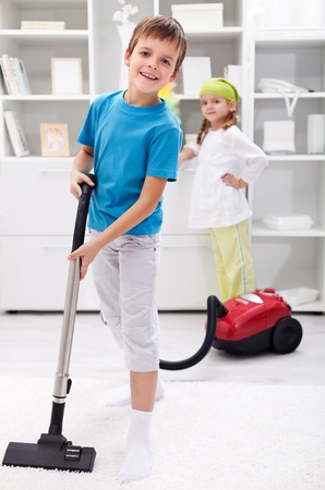 Kids cleaning the room - boy using a vacuum cleaner photo