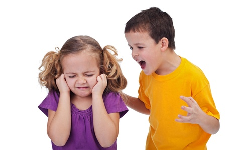 sibling rivalry: Quarreling kids - boy shouting at little girl, isolated Stock Photo