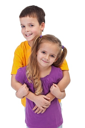 Loving siblings - little boy hugging his smaller sister, isolated Stock Photo - 12477526