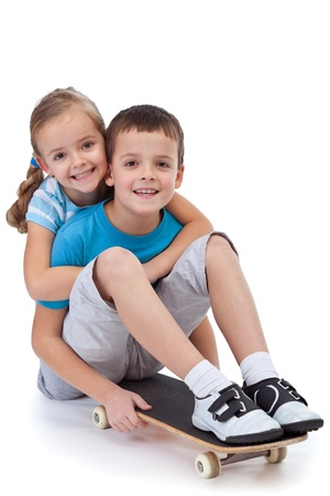 children  play: Happy kids with skateboard hugging and smiling Stock Photo
