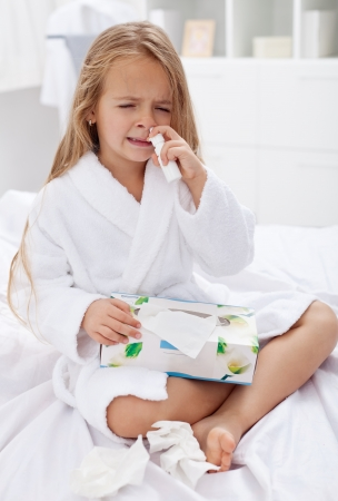 catarrh: Little girl with a bad case of influenza using nasal spray and a box of paper tissues Stock Photo