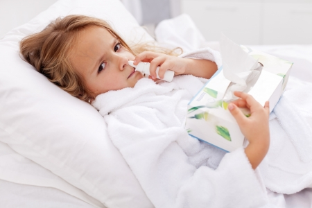 catarrh: Little girl with bad cold in bed - using nasal spray and paper napkins Stock Photo