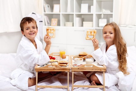egg laying: Breakfast in bed with happy kids having a healthy and varied meal