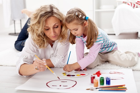 daughter: Little girl painting with her mother laying on the floor Stock Photo