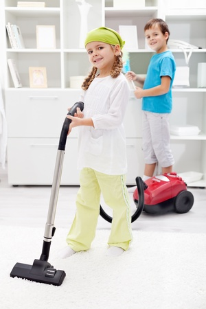 Kids cleaning the room - using vacuum cleaner and dust brush Stock Photo