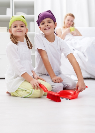 domestic chore: Kids cleaning the room helping  their sick  mother Stock Photo