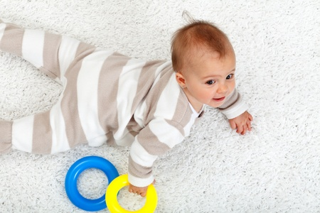 Young baby girl on the floor crawling on her belly