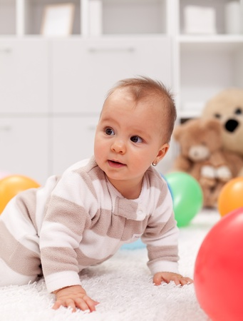 baby crawling: Baby girl with balloons - crawling on the floor
