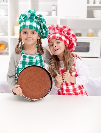 cooking utensil: Little chefs baking a cake - smiling with cooking utensils in the kitchen