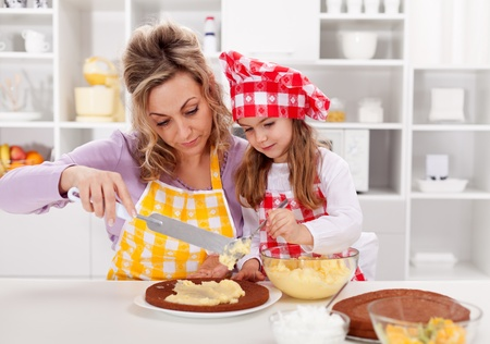 Making a cake together - woman and little girl in the kitchen photo