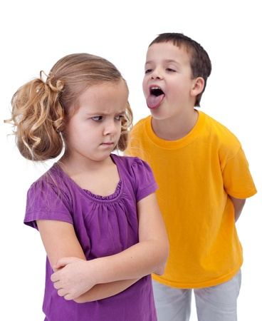 sad lonely girl: Upset little girl bullied and mocked by older boy - isolated Stock Photo