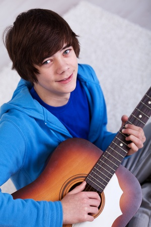 Happy teenager with guitar - closeup photo