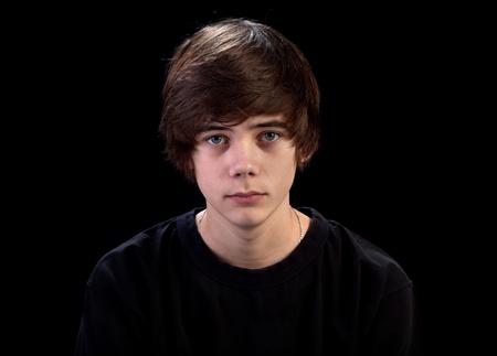 Sad teenager portrait isolated on black background photo