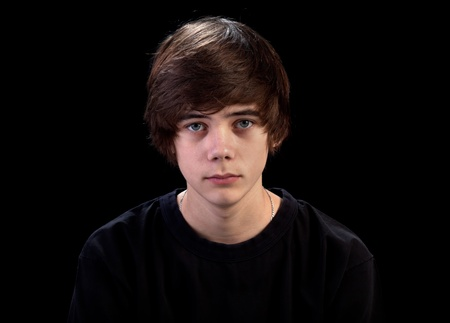 teenage boy: Sad teenager portrait isolated on black background Stock Photo