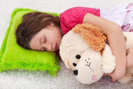 Sweet tranquility - young girl take a nap with her favorite plush toy Stock Photo