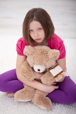 Sad young girl sitting on the floor with her teddy bear Stock Photo - 12478087