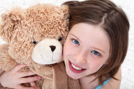 The beauty of childhood - girl with teddy bear and amazing eyes, closeup photo