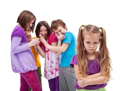 bully: Group of kids bullying and mocking their colleague - an upset little girl Stock Photo