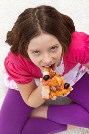 Young girl eating pizza sitting on the floor photo