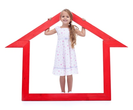 This is my new home - happy little girl with house shaped frame Stock Photo - 12478525