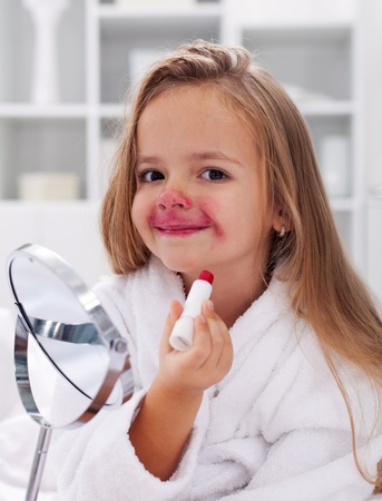 Little smiling girl playing with red lipstick and mirror  photo