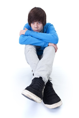 Sad teenager thinking and daydreaming while sitting on the floor - isolated photo