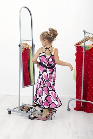I am pretty - little girl with large clothes looking to the mirror