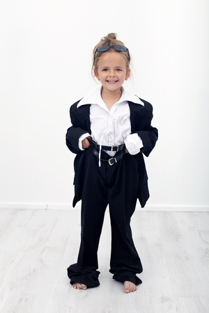 Dress up like my mother - happy little girl playing with large clothes photo