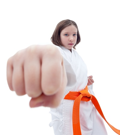 Serious karate girl with her fist in foreground - isolated photo