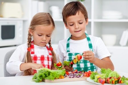 preparing food: Kids with aprons preparing a healthy vegetables meal in the kitchen