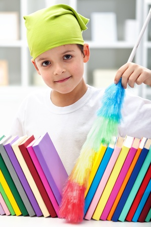 dusting: Cleaning my room - young boy with brush dusting books Stock Photo