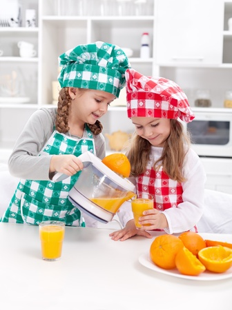 Girls making fresh and healthy orange juice with kitchen appliance
