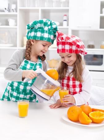 kitchen appliance: Girls making fresh and healthy orange juice with kitchen appliance Stock Photo