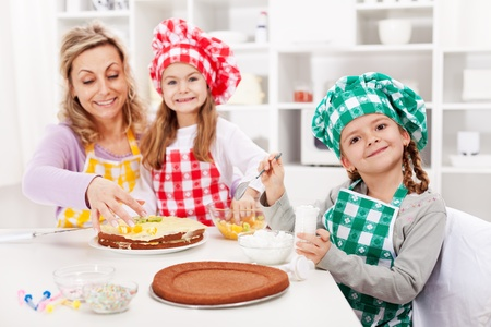Happy kids and their mother making a cake in the kitchen - focus on the front photo
