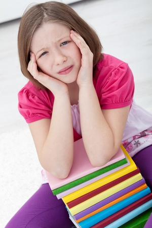 Young girl with headache sitting with lots of books photo
